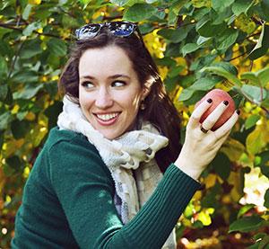 девушка рвет яблоко с дерева
