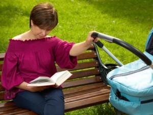 мама читает книгу во время прогулки