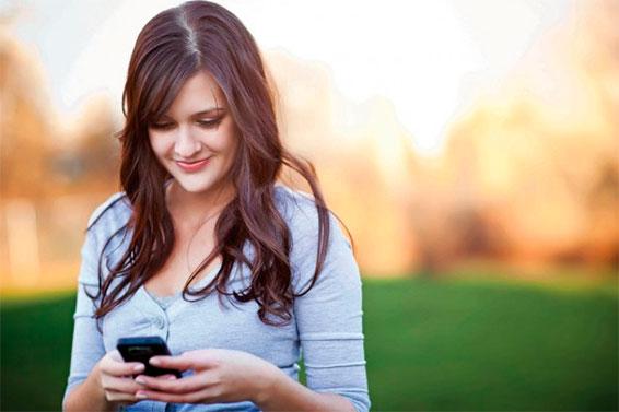 Девушка читает смс в телефоне